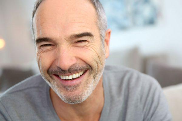 Zahnzusatzpflege lachender Mann